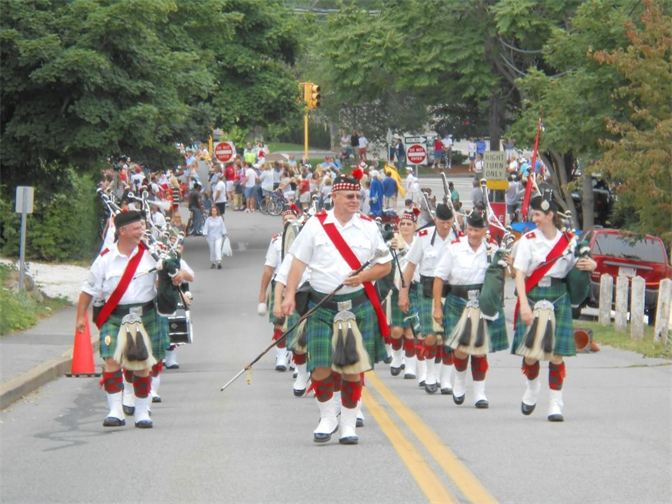 Lead by the drum major, the Highland Light Scottish pipe band marches down the street during a summer parade performance.